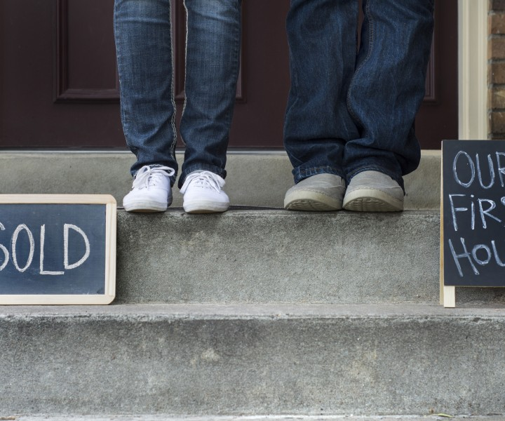 couples feet in front of house with our first house and sold sign